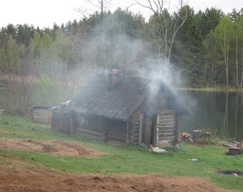 Русскую баню по-чёрному можно всегда определить по дыму, который выходит из всех щелей, дверей и окон бани