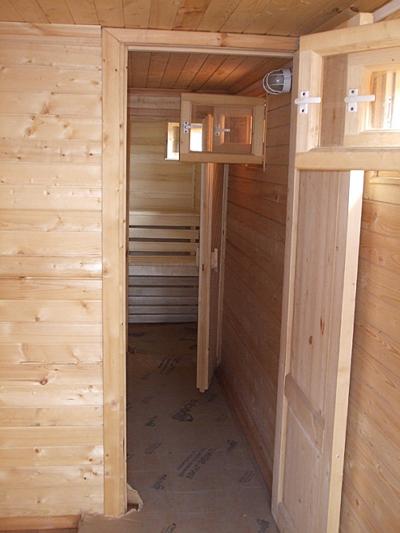 Отделанная вагонкой баня с открытыми современными окнами