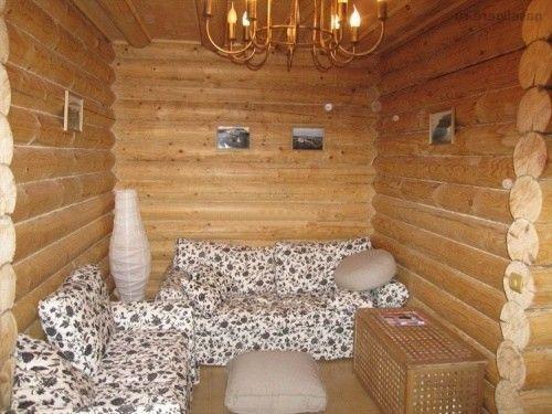 Комната отдыха в бане из брёвен с диванами для отдыха